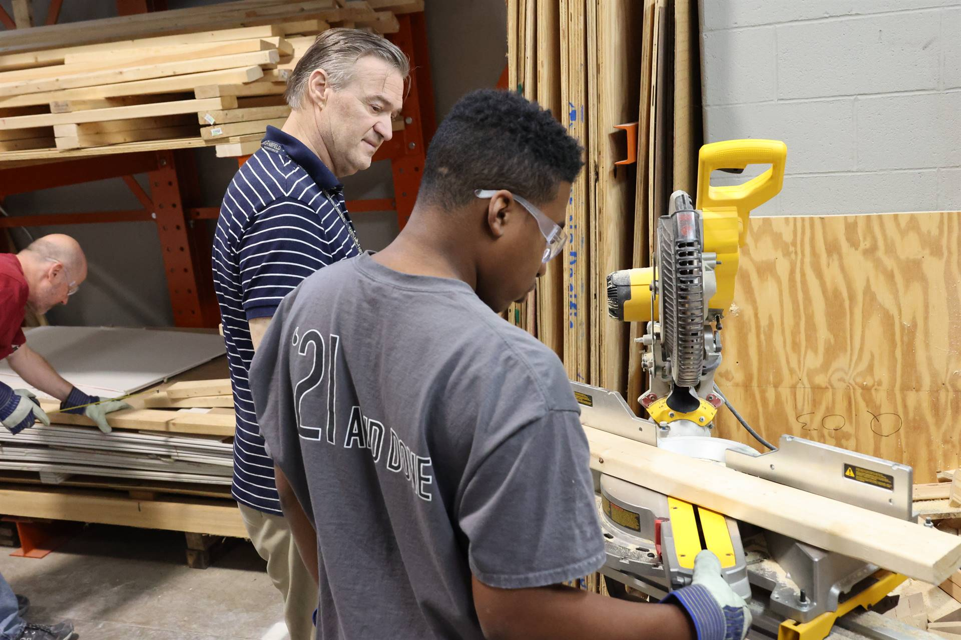 Instructor teaching students about about band saw