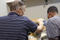 Instructor guiding student to make cut on band saw