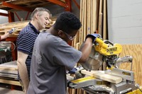 student making cut on band saw with instructor supervising