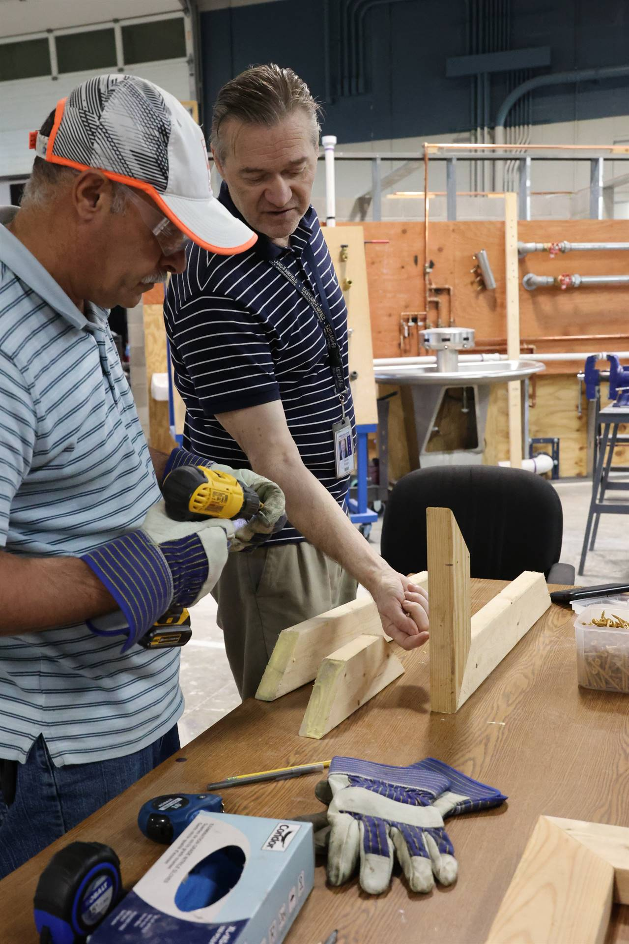 Instructor advising student on wood structure