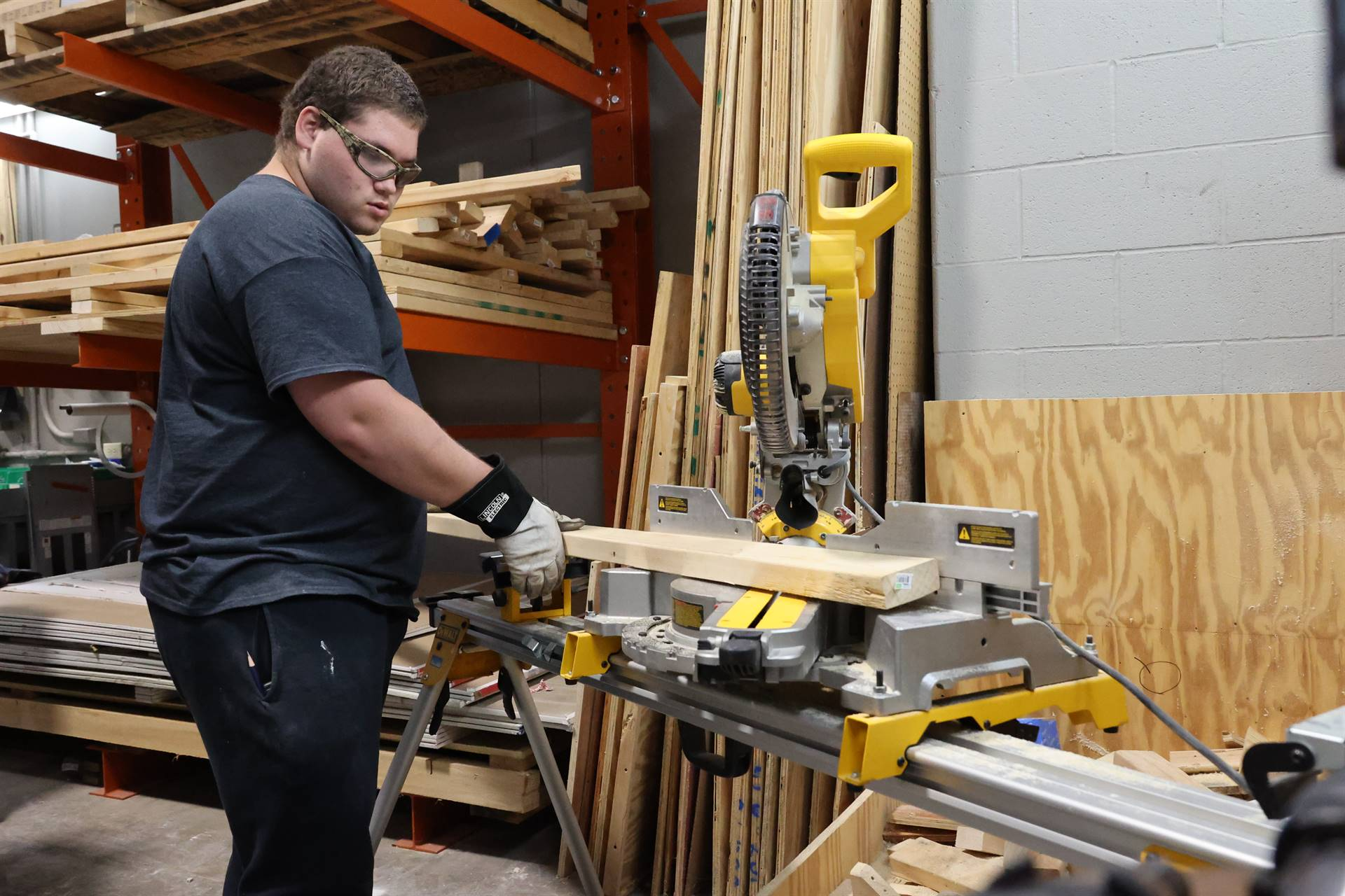 student making cut on band saw
