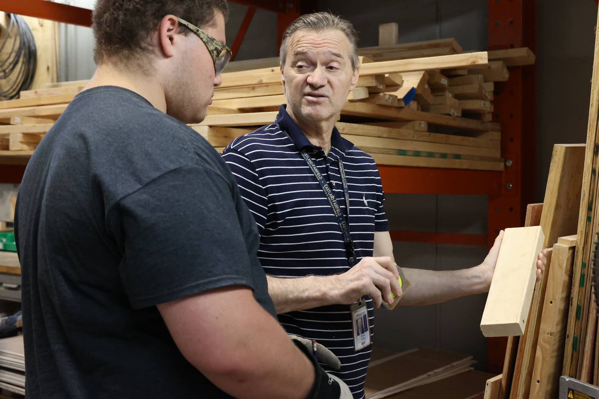 instructor talking to student while holding wood block